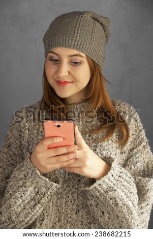 Teen girl using a smartphone and smiling - stock photo