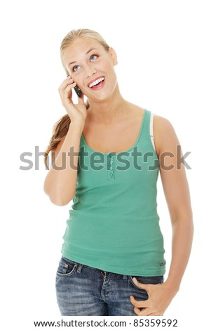 Teen girl using cell phone. Isolated on white background. - stock photo