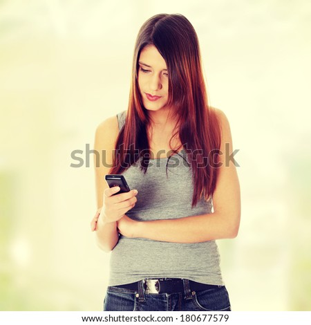 Teen girl using cell phone sending sms - stock photo