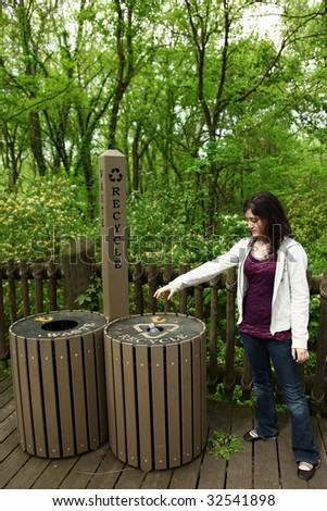 Teen girl using recycle and waste cans at park. - stock photo