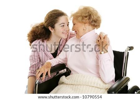 Teen girl visiting her elderly grandmother.  Isolated on white. - stock photo