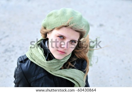 teen girl wearing green beret and scarf in windy day - stock photo