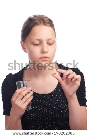 Teen girl with a pill and glass of water - stock photo