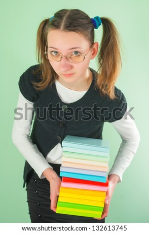 Teen girl with a stack of books against light green background - stock photo