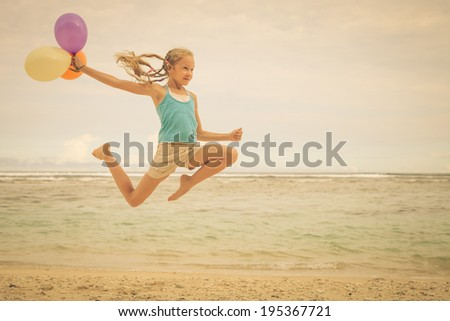 teen girl with balloons   jumping on the beach at blue sea shore in summer vacation at the day time - stock photo