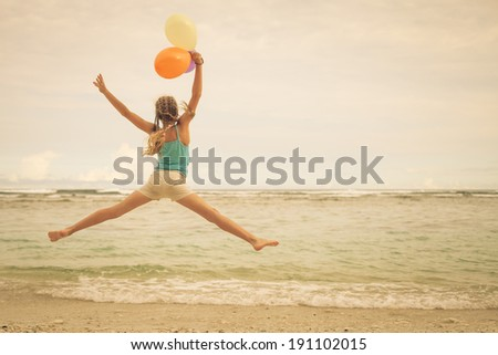 teen girl with balloons  jumping on the beach at blue sea shore in summer vacation in the day time - stock photo
