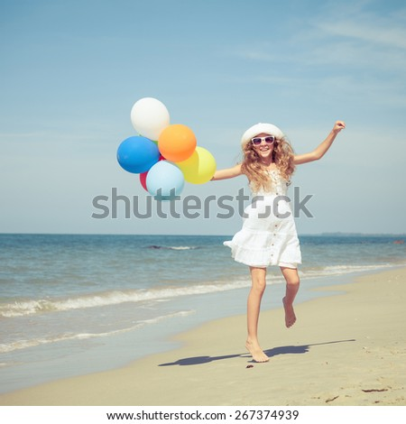 Teen girl with balloons jumping on the beach at the day time - stock photo
