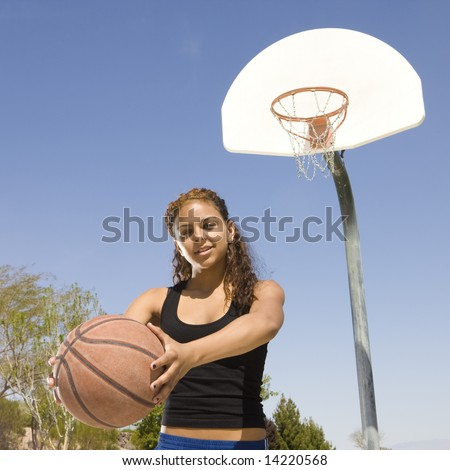 Teen girl with basketball hangs out at a basketball court - stock photo