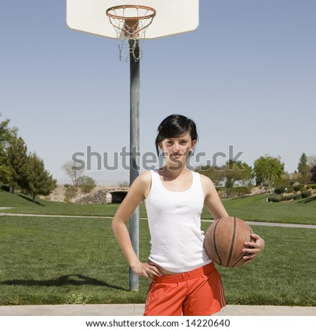 Teen girl with basketball hangs out at a park - stock photo