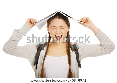 Teen girl with book over her head. - stock photo