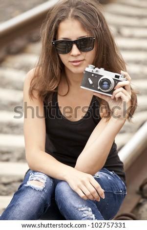 Teen girl with camera at railways. - stock photo