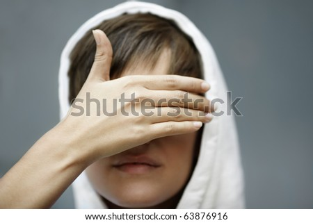 teen girl  with eyes covered by hand, selective focus on foreground - stock photo