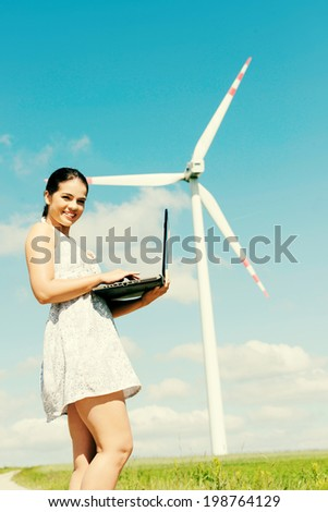 Teen girl with laptop computer next to wind turbine. Ecology - renewable energy concept.