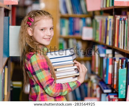 teen girl with pile books in the library - stock photo