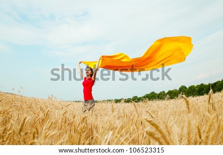 Teen girl with yellow fabric at the wheat field in sunny day - stock photo