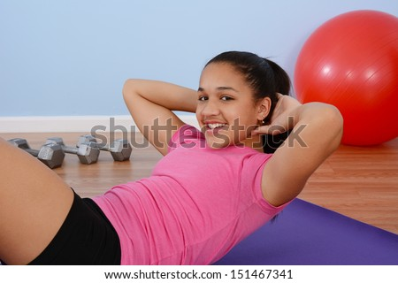 Teen girl working out in the gym