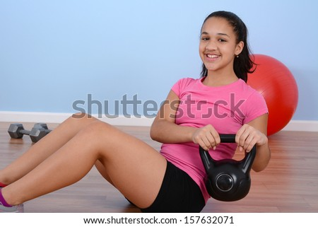 Teen girl working out while at the gym