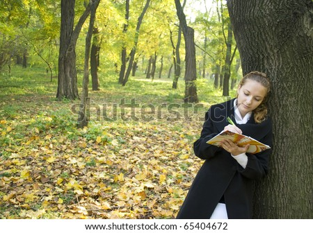 Teen girl writes a poetry in gold autumn park - stock photo