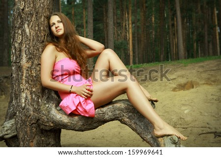 Teen girl 16 years old, Caucasian appearance, in pink dress, rest on nature, in  pine forest. Slender girl with long brown hair and bare feet, relaxing in a forest clearing, sitting on a pine branch.