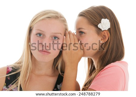 Teen girls are whispering gossip to each other - stock photo
