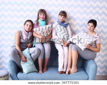 teen girls in pajamas with pillows on the sofa