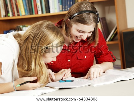 Teen girls in school library laughing as they do their homework. - stock photo