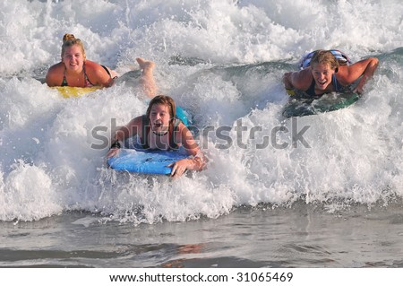 Teen girls riding wave on bodyboards.