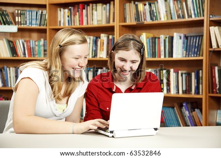 Teen girls using a netbook to do research in the library.  Room for Text - stock photo