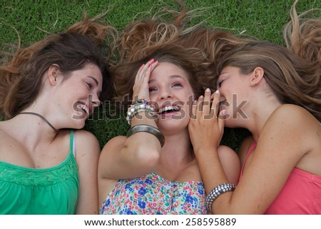 teen girls whispering and gossiping secrets in summer holidays - stock photo