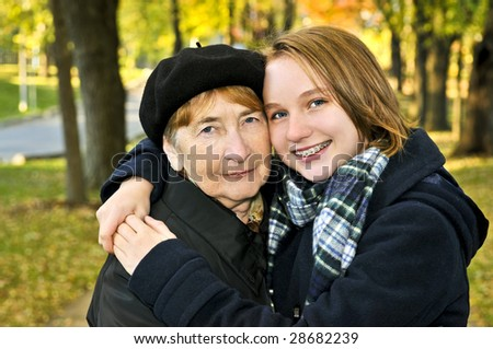 Teen granddaughter hugging grandmother in autumn park - stock photo