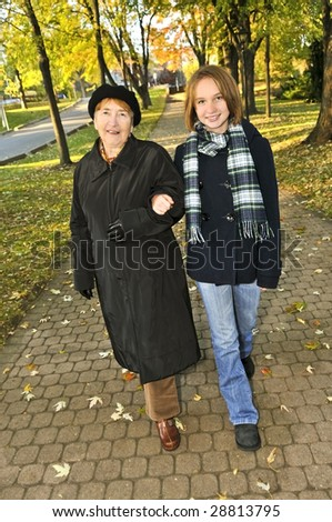 Teen granddaughter walking with grandmother in autumn park - stock photo