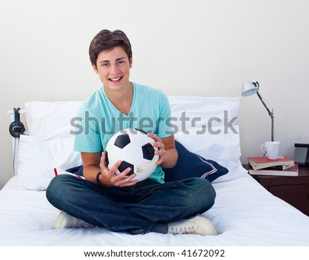 Teen guy holding a soccer ball in his bedroom - stock photo