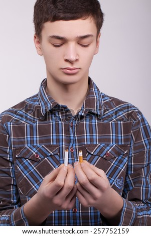 Teen guy with a cigarette in hand - stock photo