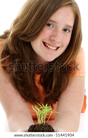 Teen holding a plant in pile of dirt - stock photo