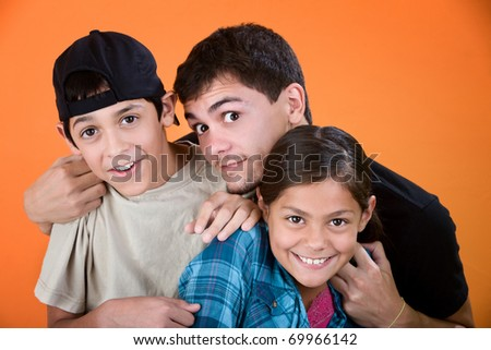 Teen holding and playing with brother and sister on an orange background - stock photo
