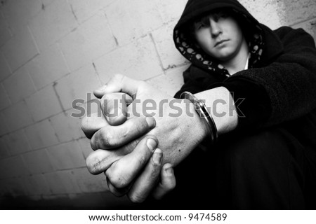 teen in handcuffs, young teen against wall with dirty hands and handcuffs, converted to black and white with slight added grain. focus on cuffs. - stock photo