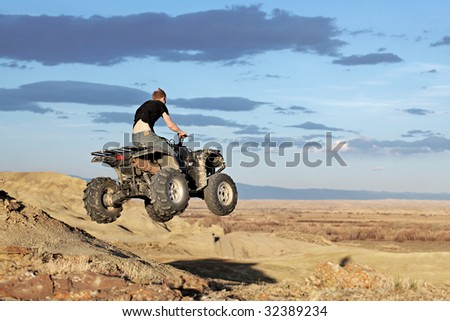 teen jumping on a quad - four wheeler 4x4 gets some air - stock photo
