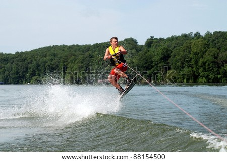 teen jumping on wake board - stock photo
