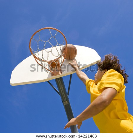 Teen jumps to dunk a basketball - stock photo