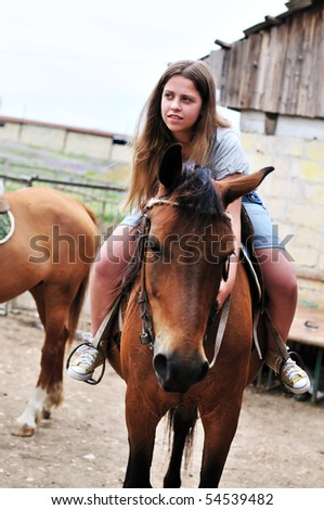 teen longhaired girl sitting on the horse