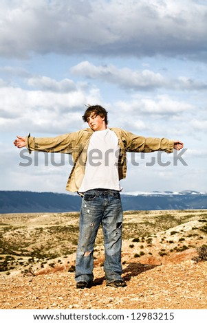teen male standing in the wind on the edge of a cliff, arms wide open - stock photo