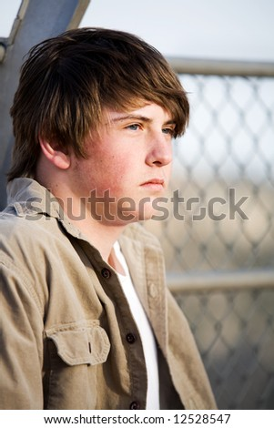 teen male with natural look, unshaven, against a fence