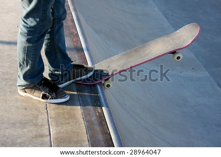 Teen on a skateboard in a starting position to go down a  half pipe ramp. - stock photo