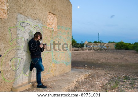 Teen playing with a console in a grunge setting - stock photo