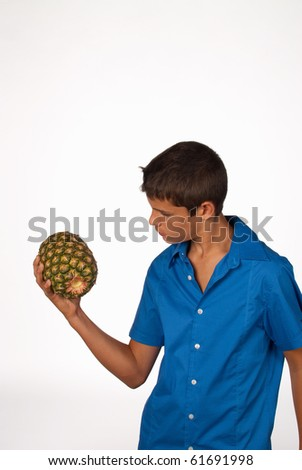 Teen practicing weightlifting with a pineapple, nutrition concept - stock photo