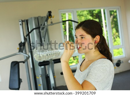 teen pretty girl drink water while work out in gym - stock photo