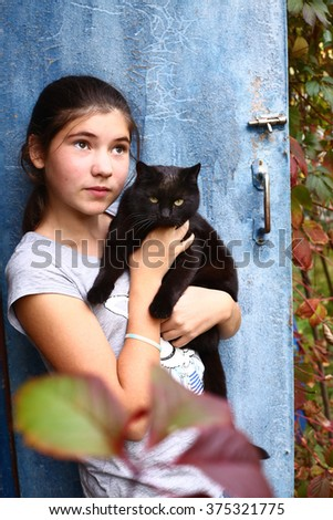 teen pretty girl wit black cat on the shabby door background - stock photo