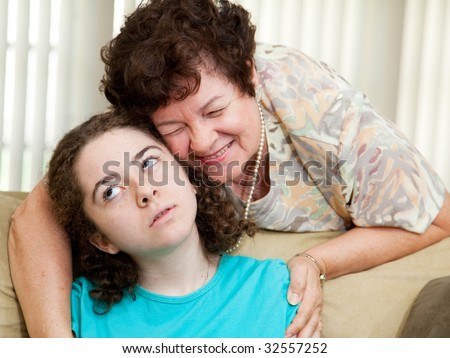 Teen puts up with a hug from an annoying aunt or parent. - stock photo