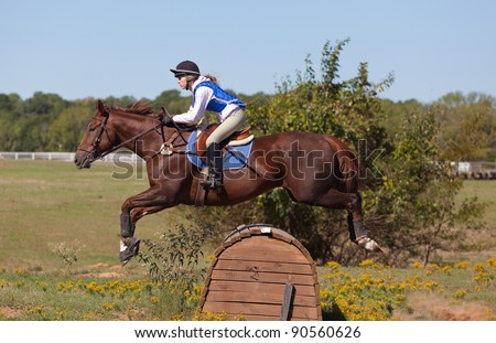 Teen rider jumps over an obstacle on a cross country course during a practice ride - stock photo