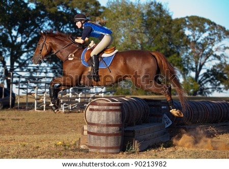 Teen rider leaps across a barrel jump on a cross country course - stock photo